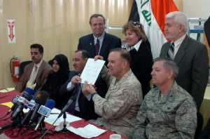 The Iraqi Deputy Minister of Education Dr. Nohad al-Jabouri and Maj. Gen. Douglas Stone hold the newly signed Memorandum of Understanding in Baghdad, Iraq, while U.S. Senator and Air Force Colonel Lindsey Graham watches Feb. 12, 2008. The document outlines the Iraqi Ministry of Education's support of the educational programming and instruction provided to detainees within the care and custody of coalition forces in Iraq. DoD photo by  U.S. Army Cpl. Chase S. Nilsen