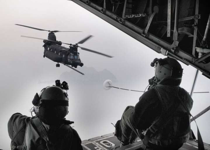 Senior Airman Meagan Freeman (left) and Airman 1st Class Jed Bilibei, both loadmasters with the 17th Special Operations Squadron, send signals from the back of an MC-130P Combat Shadow to the crew of a U.S. Army MH-47 helicopter from the 160th Special Operations Aviation Regiment (Airborne) during an aerial refueling mission near the Korean peninsula Feb. 12, 2009. U.S. Air Force photo by Tech. Sgt. Aaron Cram