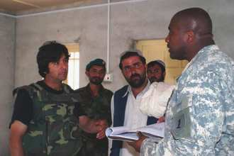U.S. Army Capt. Alton McCallum, right, discusses a contract with a local contractor, center, and Afghan National Army soldiers April 7, 2007, near Gereshk in Helmand Province, Afghanistan. The contractor was hired to assist with renovations of Afghan National Army Forward Operating Base Price; McCallum is leading the Price renovation project. (U.S. Army photo by Sgt. LeeAnn Lloyd) (Released)