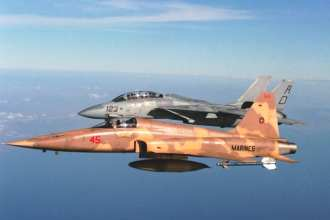 An air-to-air left-side view of a Marine Corps F-5 Tiger II aircraft, foreground, and a Navy F-14 Tomcat aircraft. Both F-5 and F-14 aircraft were sold to the government of the Shah of Iran before he was deposed. ICE has thwarted attempts to export F-5 and F-14 components to Iran, and even the attempt to send an entire decommissioned F-14 to the country. DoD photo by Lt. Baranek, USN