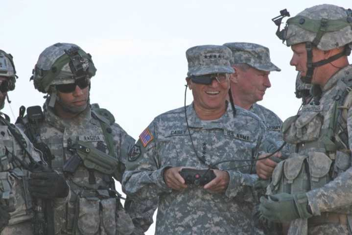 Soldiers from 5th Brigade, 1st Armored Division, Army Evaluation Task Force, watch as Army Chief of Staff Gen. George W. Casey, Jr. operates the remote control to the small unmanned ground vehicle at White Sands Missile Range, N.M. U.S. Army photo by Lt. Col. Deanna Bague, Fort Bliss Public Affairs.