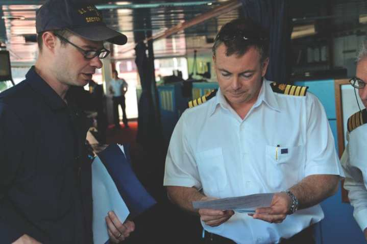 Petty Officer 1st Class Patrick Horan, a member of Coast Guard Sector Juneau inspections department, goes over pertinent information with Justin S. Lawes, captain of the cruise ship Royal Princess in Juneau, Alaska, May 27, 2010. The National Maritime Center is the licensing authority for the U.S. Coast Guard whose mission is to issue credentials to fully qualified mariners in the most effective and efficient manner possible in order to assure a safe, secure, economically efficient, and environmentally sound Marine Transportation System. U.S. Coast Guard photo by Petty Officer 3rd Class Jon-Paul Rios