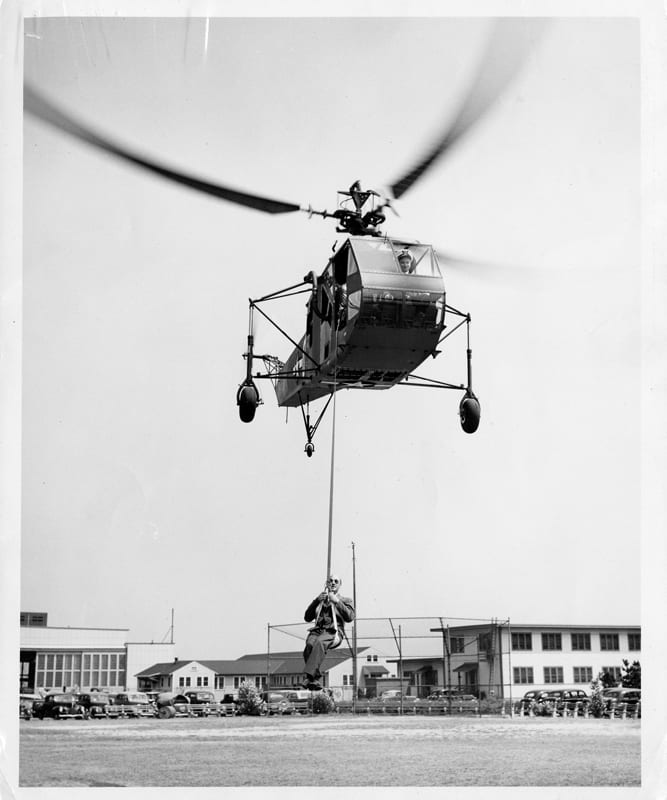 Coast Guard aviator Frank Erickson pilots an HNS while hoisting the helicopter's designer, Igor Sikorsky, during a demonstration. The early hoists were made from a parachute harness. U.S. Coast Guard photo