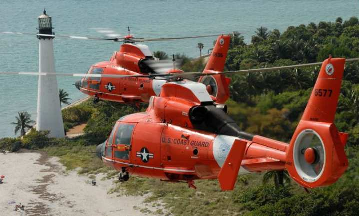 Two Coast Guard HH-65C Dolphin helicopters from Air Station Miami pass by the Cape Florida Lighthouse in Key Biscayne, Fla., Nov. 11, 2007. The HH-65 is know for its Fenestron tail rotor and its autopilot capabilities, which can complete an unaided approach to the water and bring the aircraft into a stable 50-foot hover, or automatically fly search patterns, an ability that allows the crew to engage in other tasks. U.S. Coast Guard photo by PAC Dana Warr