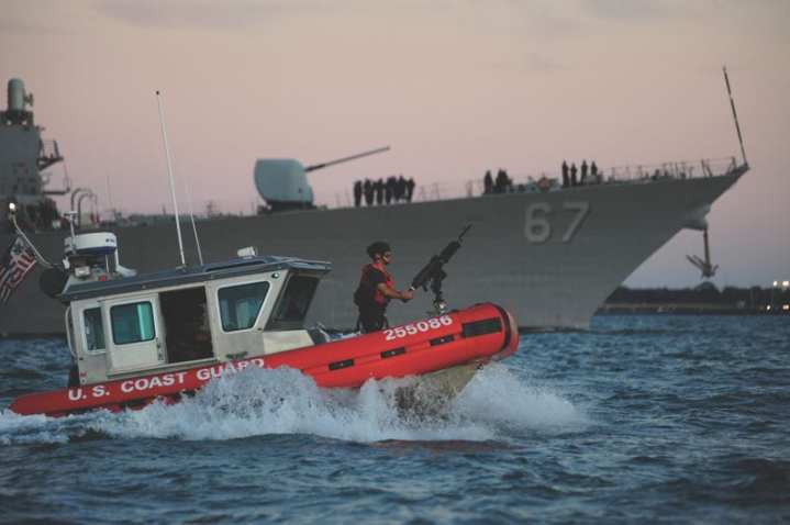 A Coast Guard Maritime Safety and Security Team crew, temporarily deployed from San Francisco, provides an escort for the USS Cole as the Navy destroyer returns to the Norfolk Naval Shipyard, Aug. 31, 2011. Coast Guard crews provided security zones for the Navy ships returning to harbor after Hurricane Irene. The Navy had ordered ships to head out to safer waters to protect them from the approaching storm. U.S. Coast Guard photo by Petty Officer 3rd Class David Weydert