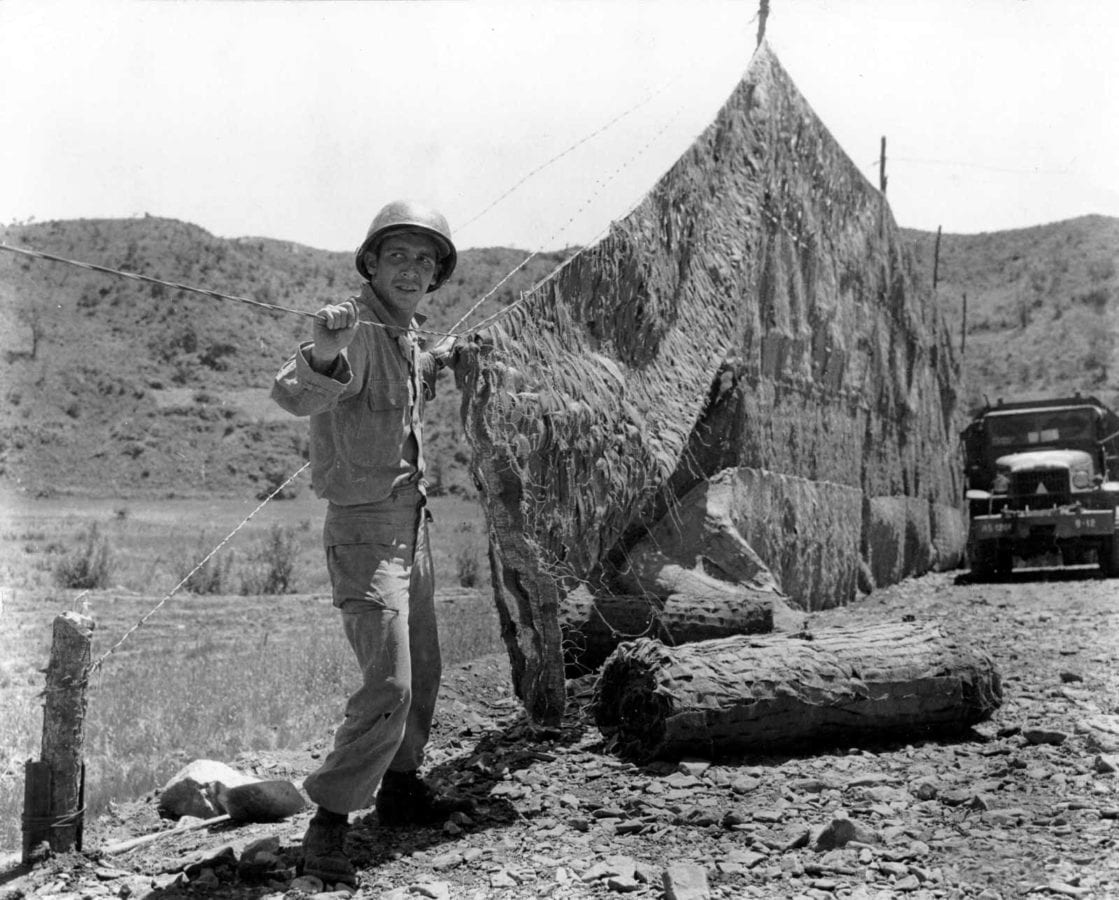 US Army Soldier With 20th Engineer Battalion 45th Infantry Division Erects A Camouflage Net Over Road Exposed To The Enemy In Korea June 7 1952