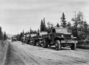 U.S. Army dump trucks line the road with gravel along the Alcan Highway route, ca. 1942. Library of Congress photo