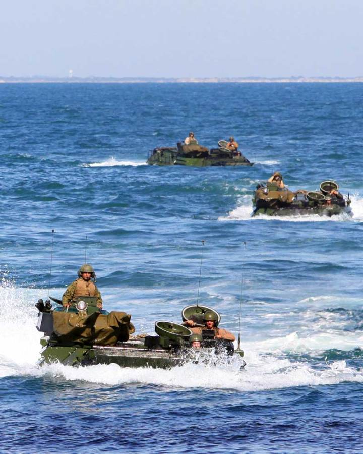 Assault amphibious vehicle (AAV) crewman from 2nd Assault Amphibian Vehicle platoon, Battalion Landing Team 1st Battalion, 2nd Marine Regiment, 24th Marine Expeditionary Unit (MEU) make their way to the well deck of the amphibious assault ship USS Iwo Jima from the USS New York on Oct. 26, 2011. The AAVs practiced loading and offloading from the Iwo Jima as part of the Amphibious Squadron 8 (PHIBRON 8)/MEU Integration Exercise, known as PMINT. Modernization of the AAVSs, as well as procurement of a next-generation Amphibious Combat Vehicle (ACV), are top priorities for the Marine Corps. U.S. Marine Corps photo by Lance Cpl. Michael J. Petersheim