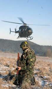 A Bulgarian soldier watches a U.S. medical evacuation UH-72 Lakota helicopter prepare to land during Operational Mentor Liaison Team training at the Joint Multinational Readiness Center (JMRC) in Hohenfels, Germany, Jan. 18, 2012. U.S. Army photo by Spc. Ashley Webster
