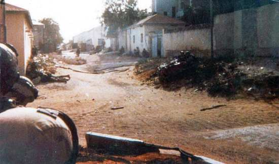 The only photo released of the battlefield on the day of the battle, with TF Ranger personnel shown taking cover alongside buildings near the crash site. U.S. Army photo