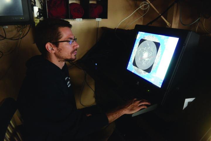 Alex Balsley, a program manager with the Coast Guard Research and Development Center in New London, Connecticut, reads an ice radar display while underway in the Arctic aboard the CGC Healy Aug. 17, 2014. The Coast Guard was evaluating the system as part of its Arctic Strategy to test and refine the capabilities of Arctic resource requirements. U.S. Coast Guard photo by Petty Officer 1st Class Shawn Eggert