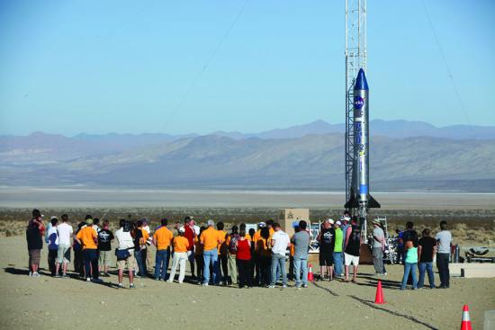 In the Mojave Desert in California, students and engineers participate in a pre-launch briefing before the lift off of the Garvey Spacecraft Corporation's Prospector P-18D rocket. The rocket was scheduled to launch the RUBICS-1 payload on a high-altitude, suborbital flight. The rocket carried four satellites made from 4-inch cube sections. Collectively known as CubeSats, the satellites were designed to record shock, vibrations, and heat inside the rocket. Built by several different organizations, including a university, a NASA field center, and a high school, the spacecraft were 4-inch cubes designed to fly on their own eventually, but will remain firmly attached to the rocket during the mission. NASA/Dimitri Gerondidakis