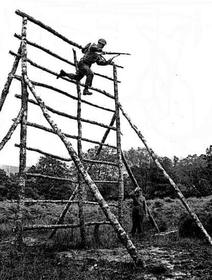 A Ranger leaps from an obstacle during training. The British Commando standing by seems to be dreading the coming impact with the ground.