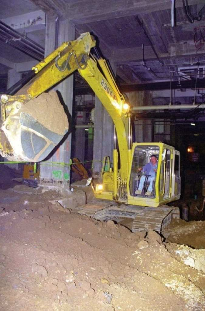 The sheer size of the Pentagon is evident as a worker uses an excavator inside the buiding to dig a trench during renovation. National Archives via Picryl