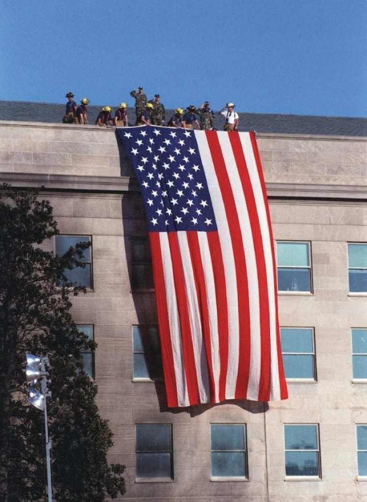 "Fire fighters and military personnel on the roof of the Pentagon unfurl a large American Flag during the Sept. 12, 2001, visit of President George W. Bush to the site of the previous day's terrorist attack on the Pentagon. As the flag was draped over the wall, just south of the site where American Airlines Flight 77 impacted the building, the disaster workers gathered around the president began to sing ""God Bless America."" DoD photo by R. D. Ward"