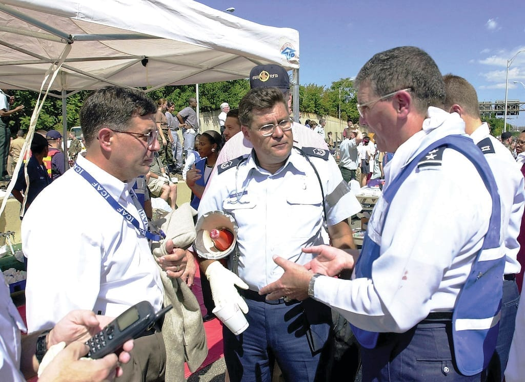 Lt. Gen. (Dr.) Paul Carlton Jr., surgeon general of the Air Force (right), Master Sgt. Noel Sepulveda, USAF (center), and Pentagon employees pitch in to help where needed after a hijacked American Airlines flight deliberately crashed into the Pentagon Sept. 11, 2001. DoD photo