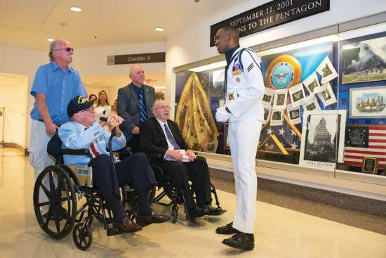 Navy Seaman Shakeem Serville gives a guided tour to USS Arizona survivors, seated, at the Pentagon in Arlington, Virginia, July 17, 2017. The Arizona was attacked at Pearl Harbor at the beginning of World War II. DOD Photo by U.S. Army Sgt. James K. McCann