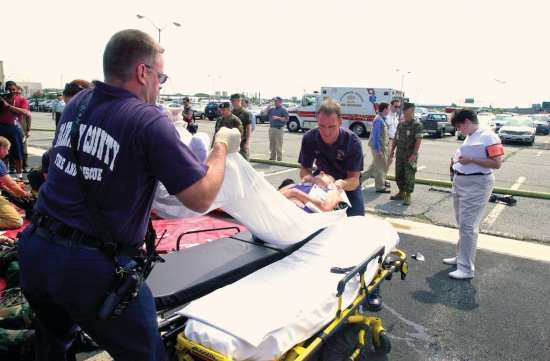 Paramedics from Fairfax County, Virginia, Fire and Rescue move a casualty from a gurney to a stretcher for transportation to a local hospital during Exercise Gallant Fox outside of the Pentagon. The purpose of Gallant Fox was to enable the Pentagon Force Protection Agency (PFPA) to exercise emergency response units in a real world scenario and provide valuable training for PFPA to better serve occupants of the Pentagon. U.S. Marine Corps photo by Cpl. Eugene Clarke