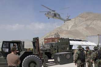 An MH-60S Knighthawk assists Navy Seabees construction personnel in offloading of 1,200 tons of construction equipment and supplies from the USS Saipan (LHA 2) during support exercise New Horizons, in Gonaives, Haiti, in February 2005. U.S. Navy image