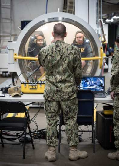 Research Physiologist Lt. Travis Doggett, center, directs aircrew via radio during simulated flight in the Fluctuating Altitude Simulation Technology (FAST) system Jan. 14, 2019 at Navy Experimental Diving Unit. The system was developed and built by Naval Surface Warfare Center Panama City Division. (U.S. Navy photo by Anthony Powers/Released