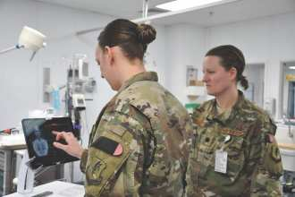 Capt. Katie Barnack (left), an emergency room nurse, and Lt. Col. Valerie Sams, a trauma surgeon, both deployed with the 455th Expeditionary Medical Group, demonstrate the T6 Health System, which is in trial phase at the Craig Joint Theater Hospital at Bagram Airfield, Afghanistan, March 30, 2019. The T6 mobile device application is a high-resolution, digital documentation system that may be used to replace some paper records and streamline patient care processes. U.S. Air Force Photo by Capt. Anna-Marie Wyant