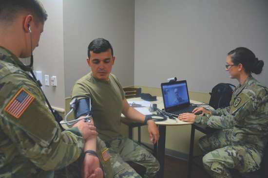 """Mobile medic Spc. Amanda Knight prepares for a video conference with a medical provider while mobile medic Spc. Joshua Rath checks Spc. Joao Dos Santos Faustino's vitals during an early morning """"sick call"""" at the 232nd Medical Battalion, Sept. 25, 2017. A team of mobile medics used a combination of virtual and hands-on health care to triage the soldiers who reported to morning sick call. U.S. Air Force photo by Robert Shields"""