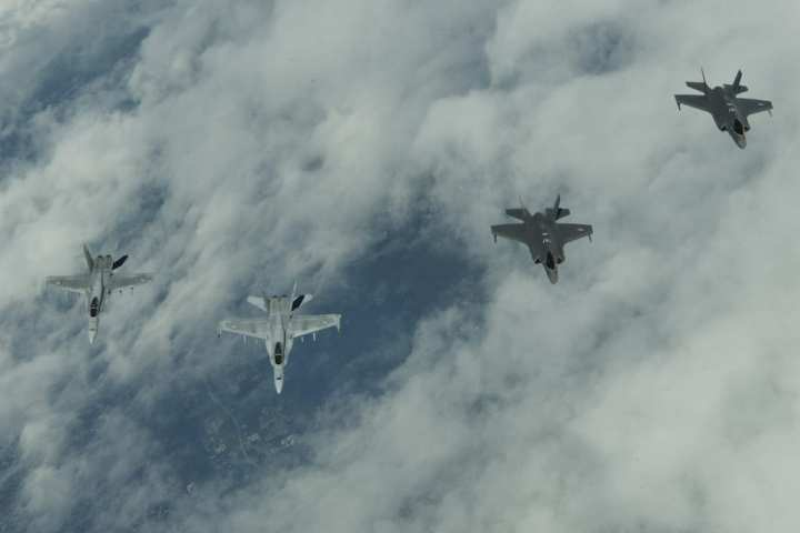 Two U.S. Air Force F-35A Lightning II fighter aircraft, assigned to the 421st Fighter Squadron, Hill Air Force Base, Utah, right, fly in formation with two Finnish F-18 Hornets, left, while en route to Turku, Finland, June 13, 2019. These aircraft are in Europe to participate in exercises and conduct training with Europe-based aircraft in support of a Theater Security Package.