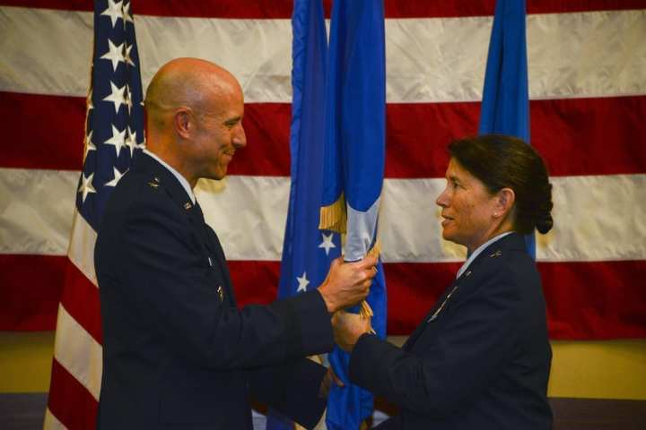 Brig. Gen. David Tabor, Joint Special Operations Command assistant to the deputy commander and assistant commanding general, presents the brigadier general flag to Brig. Gen. Brenda Cartier, Air Force Special Operations Command's director of operations, June 14, 2019, at Hurlburt Field, Florida. Cartier is AFSOC's first female general officer. (U.S. Air Force photo by Staff Sgt. Lynette Rolen)