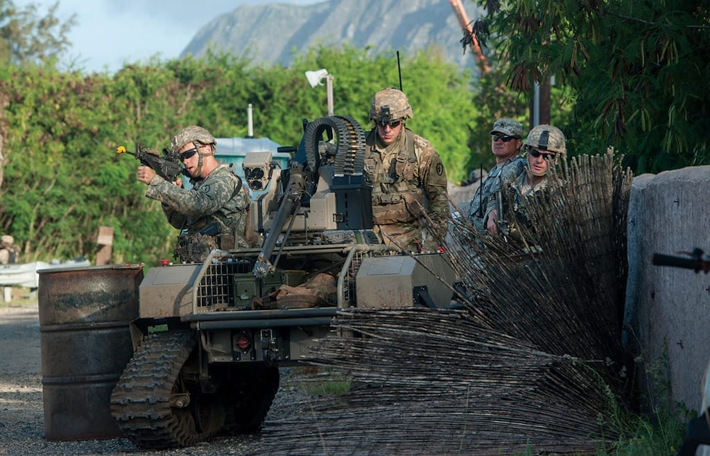 Soldiers from 2nd Battalion, 27th Infantry Regiment, 3rd Brigade Combat Team, 25th Infantry Division, move forward toward simulated opposing forces with a multipurpose unmanned tactical transport 22 July 2016 during the Pacific Manned-Unmanned Initiative at Marine Corps Training Area Bellows, Hawaii. (Photo by Staff Sgt. Christopher Hubenthal, U.S. Air Force)
