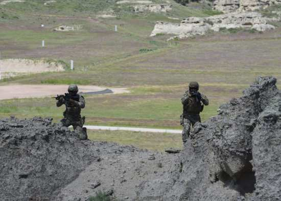 U.S. Air Force Senior Airman Ryan Mason II, 91st Security Support Squadron tactical response force member, and Senior Airman Kevin Freese, 341st Security Support Squadron TRF, navigate terrain during the advanced tactical course at Camp Guernsey, Wyo., June 19, 2019. The teams practiced infiltrating an enemy location and reacting to enemy fire.