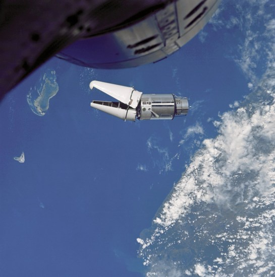 "The Augmented Target Docking Adapter (ATDA) as seen from the Gemini IX spacecraft during one of three rendezvous in space. The ATDA and Gemini IX spacecraft are 66.5 feet apart. Failure of the docking adapter protective cover to fully separate on the ATDA prevented the docking of the two spacecraft. The ATDA was described by the Gemini IX crew members as an ""angry alligator."""