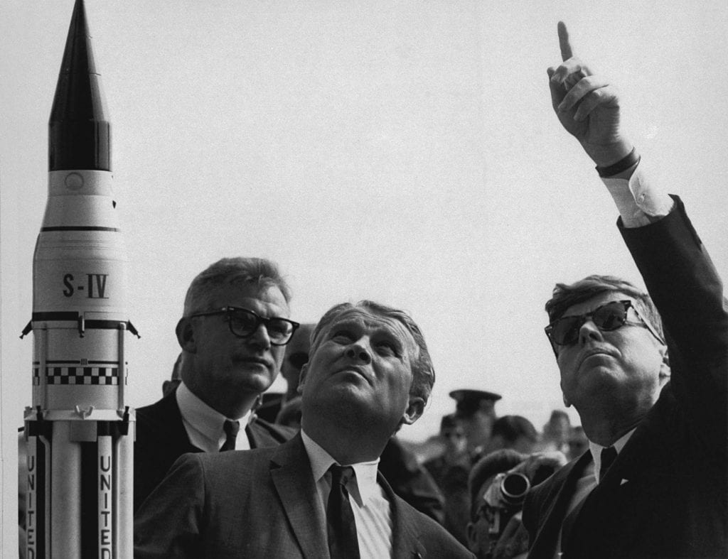 Dr. Wernher von Braun explains the Saturn Launch System to President John F. Kennedy. NASA Deputy Administrator Robert Seamans is to the left of von Braun. The powerful Saturn V booster launched American astronauts to the Moon during the Apollo program of the 1960s and 1970s. *Image Credit*: NASA