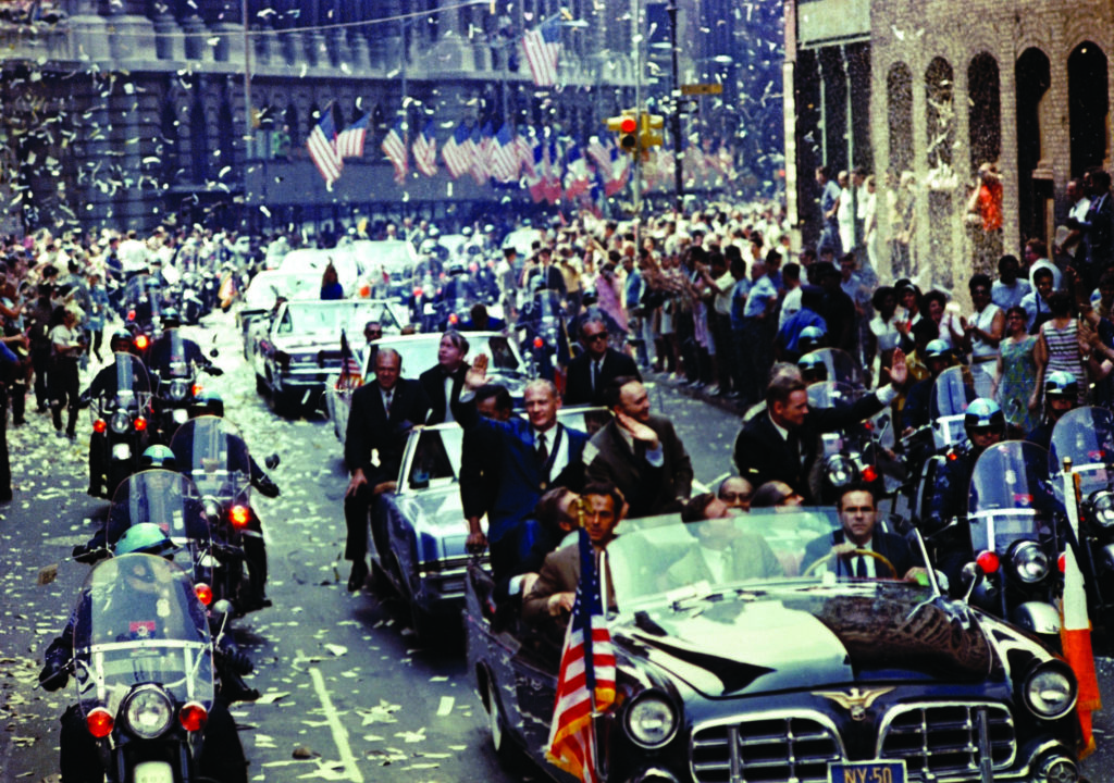 New York City welcomes Apollo 11 crewmen in a showering of ticker tape down Broadway and Park avenues in a parade described as the largest in the city's history. Pictured in the lead car, from the right, are astronauts Armstrong, Collins, and Aldrin. The three astronauts teamed for the first manned lunar landing on July 20, 1969.
