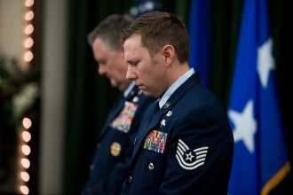 Technical Sgt. Michael Perolio, bows his head during the prayer before he was presented both the Silver and Bronze Stars, at Joint Base San Antonio-Lackland July 18, 2019. (U.S. Air Force photo by Sarayuth Pinthong)