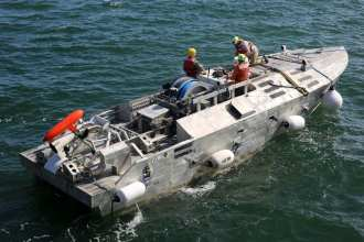 "A Sailor and civilian technicians monitor an unmanned surface vehicle (USV), after it was launched from Military Sealift Command's expeditionary sea base, USNS Hershel ""Woody"" Williams (T-ESB 4), into the Chesapeake Bay, Sept. 14. The USV is a mine counter measure platform and the evolution was the first time a USV has been launched and recovered by a Military Sealift Command ship. (U.S. Navy photo by Bill Mesta/Released)"