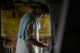 Army Master Sgt. Juan Munoz applies paint to his palette as he prepares to work on an official Army art piece.