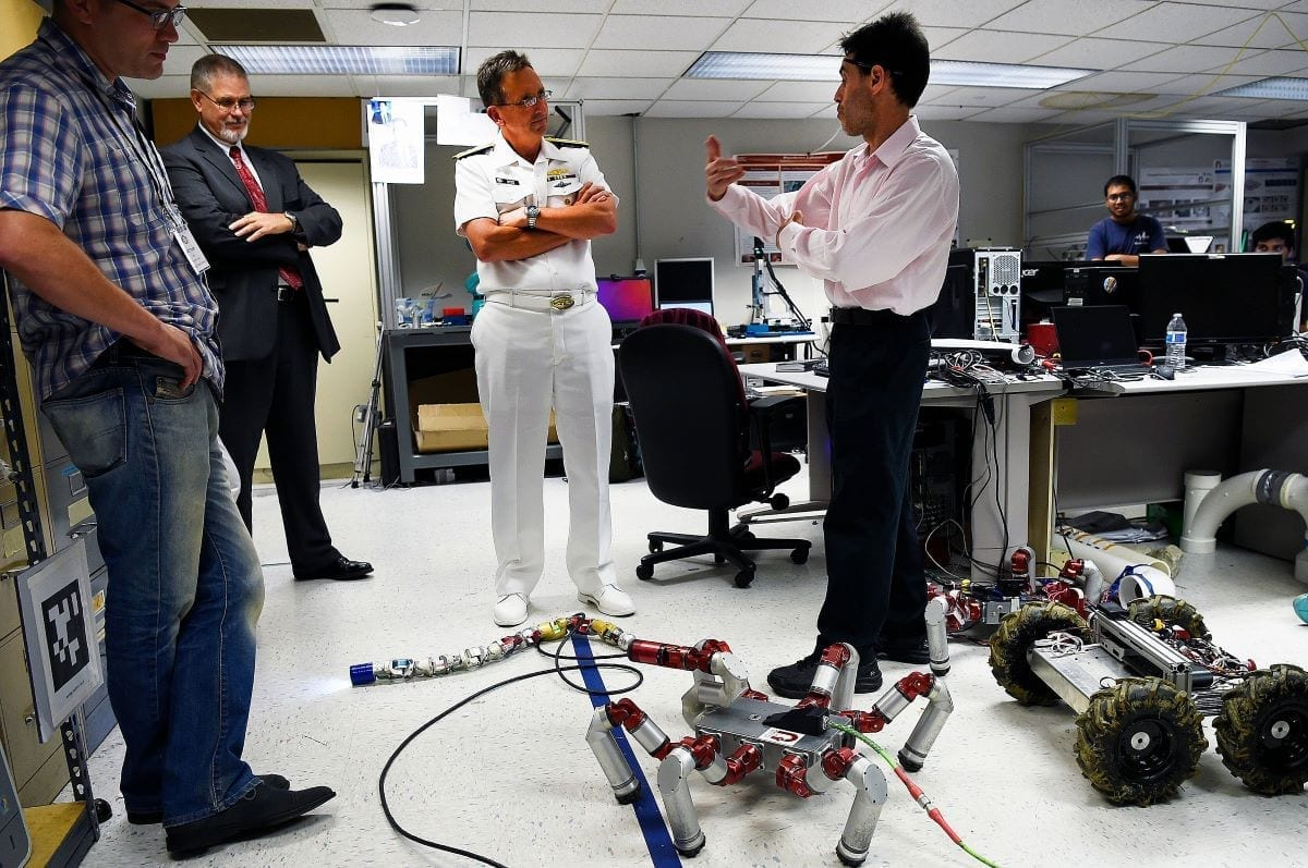 Rear Adm. David Hahn and Dr. David Walker, research and development portfolio director at the Office of Naval Research (ONR), speak with Professor Howie Choset in the Biorobotics Laboratory at Carnegie Mellon University (CMU).