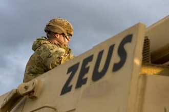 An Army Soldier with 1st Armored Brigade Combat Team, 1st Infantry Division, sits atop a staged vehicle at the port of Bremerhaven, Germany Oct. 18, 2019. The Big Red One Soldiers have been deployed throughout Eastern Europe for the last nine months as a rotational force in support of U.S. Army Europe and Atlantic Resolve. (U.S. Army photo by Sgt. Thomas Mort)
