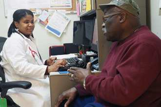 "LaCresha Mitchum, a registered nurse, certified diabetes educator, and diabetic coordinator at the Williams Jennings Bryan Dorn VA Medical Center in Columbia, South Carolina, listens to U.S. Army veteran William Baker, a patient with type 2 diabetes, as he describes some health issues. An investigation launched last year, ""Mitigating Racial/ Ethnic and Socio-e3conomic Disparities in VA Care Quality and Patient Experience"", aims to understand how better performing VA systems provide diabetes care to racial/ethnic minority veterans, with the hope that systems with better health outcomes can help other facilities or systems improve."