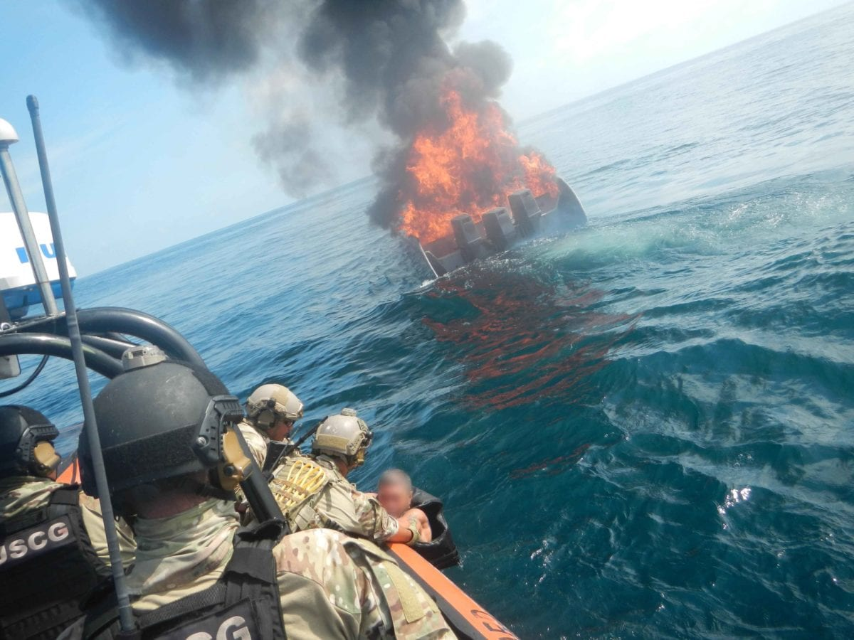 A suspected smuggler, who jumped from his burning vessel, is pulled aboard an interceptor boat from the Cyclone-class coastal patrol ship USS Zepher (PC8) by members of the U.S. Coast Guard and the Navy in international waters of the Eastern Pacific Ocean on April 7, 2018.