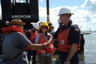 Coast Guard Incident Management and Preparedness Policy Director Dana Tulis (center) looks on as boat owner Kendrick Bragg and Coast Guard Cheif Petty Officer Travis Rogers, with the Hurricane Maria ESF-10 Puerto Rico response, exchange greetings. Salvage crews working in support of the unified command had refloated Bragg's boat, which had been grounded during Hurricane Maria, Las Croabas, Puerto Rico, Dec 13, 2017.