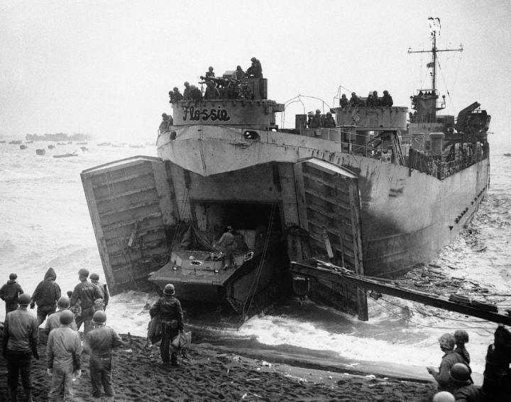 """""""Flat-nose Flossie,"""" a Landing Ship, Tank (LST), unloads a Landing Vehicle, Tracked (LVT) on the beach at Iwo Jima, Feb. 19, 1945. Specialized ships and vehicles like the LST and LVT were a vital part of United States tactics in the Pacific war. U.S. Navy Photo"""