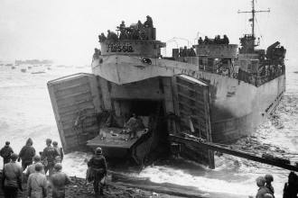 """Flat-nose Flossie,"" a Landing Ship, Tank (LST), unloads a Landing Vehicle, Tracked (LVT) on the beach at Iwo Jima, Feb. 19, 1945. Specialized ships and vehicles like the LST and LVT were a vital part of United States tactics in the Pacific war. U.S. Navy Photo"