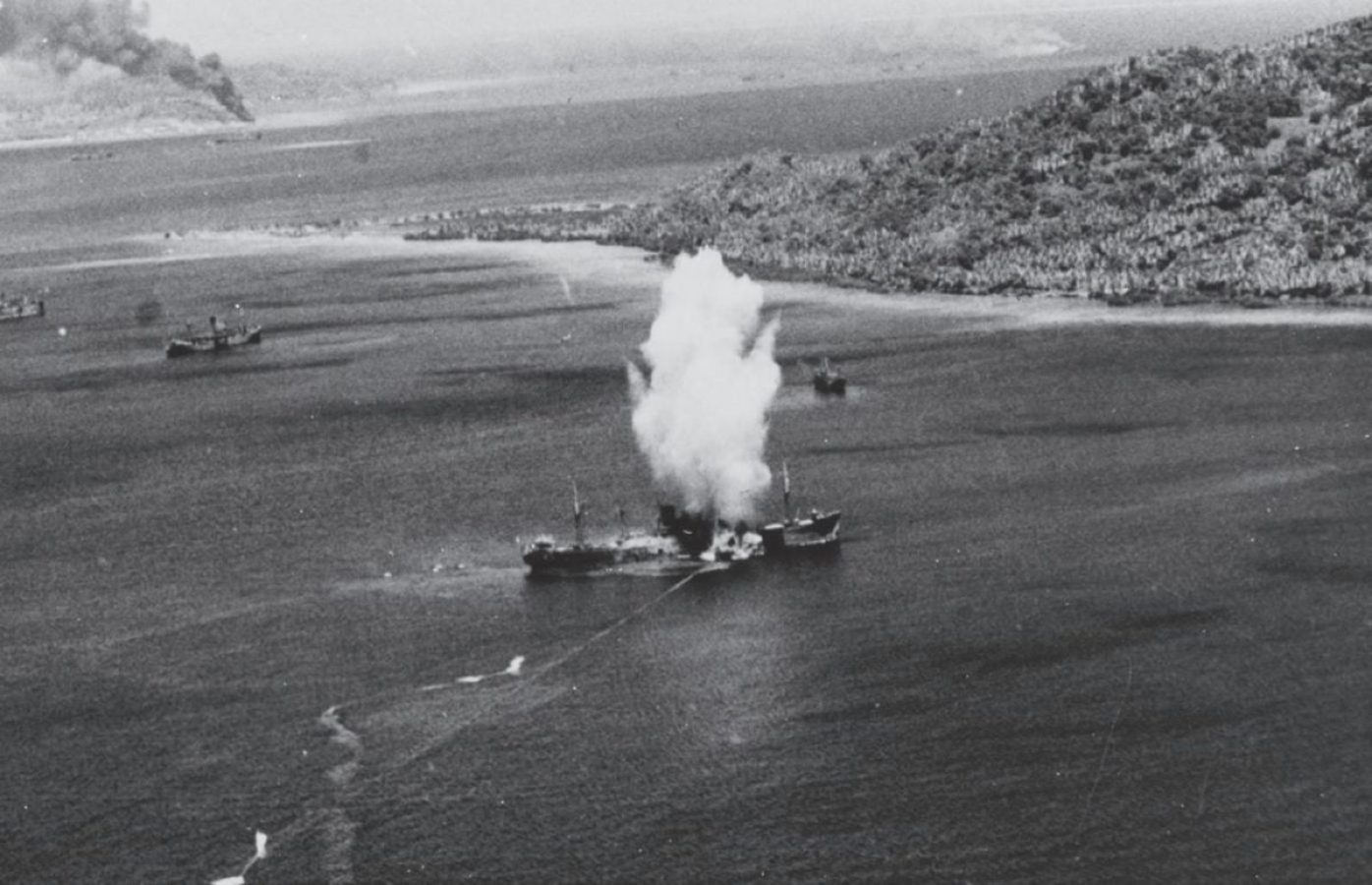"""Much preferred, if possible, over fighting bloody battles for fortified Japanese islands was to bypass them entirely, isolate them by air and sea blockade, and let them """"wither on the vine"""" as in the case of the Japanese bastions on Rabaul and Truk. Here a torpedo hits a Japanese cargo ship during the first day of U.S. Navy carrier air raids on Truk, Feb. 17, 1944. U.S. Marine Corps Photo"""