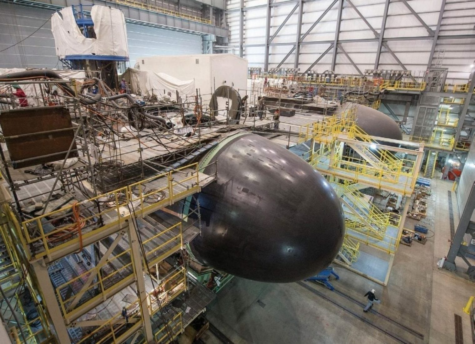 The bow units of Washington (SSN 787) and Colorado (SSN 788) fill one side of the Supplemental Modular Outfitting Facility (SMOF) at Newport News Shipbuilding. Huntington Ingalls Industries' Newport News Shipbuilding and General Dynamics Electric Boat have been sharing in the construction of the Virginia-class submarines.