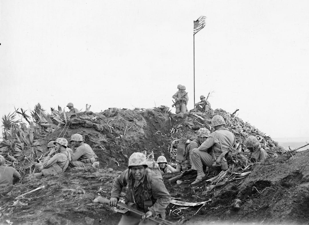 The first flag was raised on Mt. Suribachi Feb. 23, 1945, at around 10:20 a.m., but the fighting wasn't over on Suribachi, and even after the mountain was secured, the battle on other parts of the island would continue for a month. In the foreground, facing the camera, is Pfc. Louis Charlo, who was part of the earlier morning patrol that found Suribachi nearly undefended, and was present for both flag-raisings. He was killed in action a week later while attempting to rescue a wounded Marine. U.S. MARINE CORPS PHOTO BY SGT. LOUIS BURMEISTER