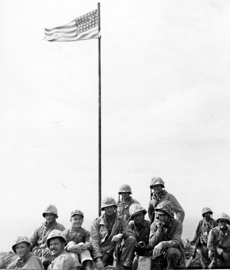 Marines from the patrol rest below the first American flag raised atop Mt. Suribachi. U.S. MARINE CORPS PHOTO