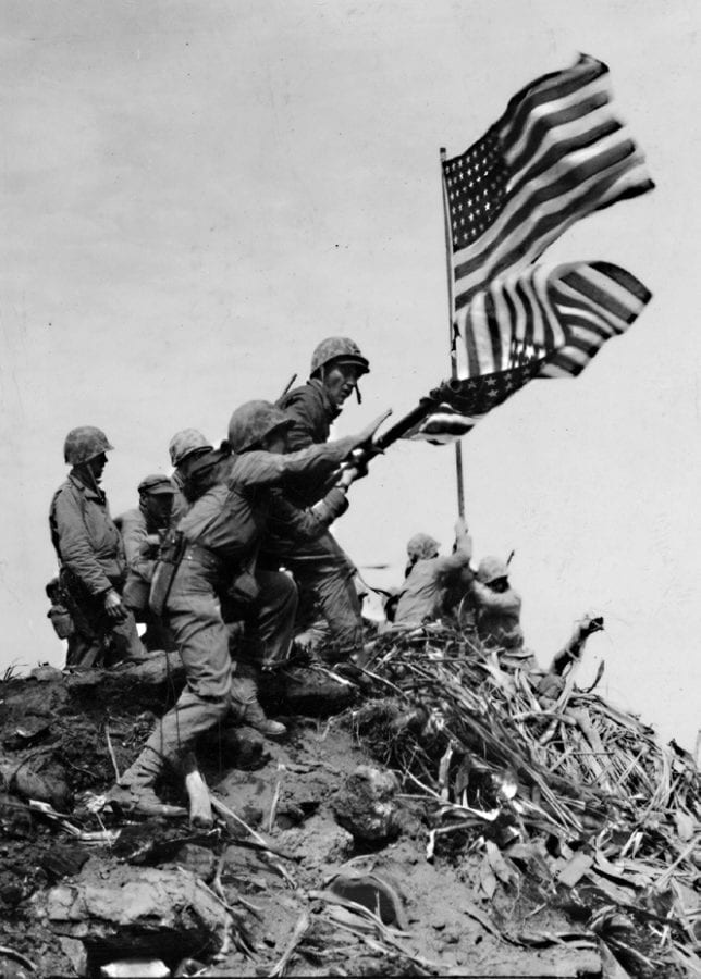 The first flag is taken down and replaced with the second, larger American flag on Mt. Suribachi. U.S. MARINE CORPS PHOTO BY PFC. ROBERT CAMPBELL