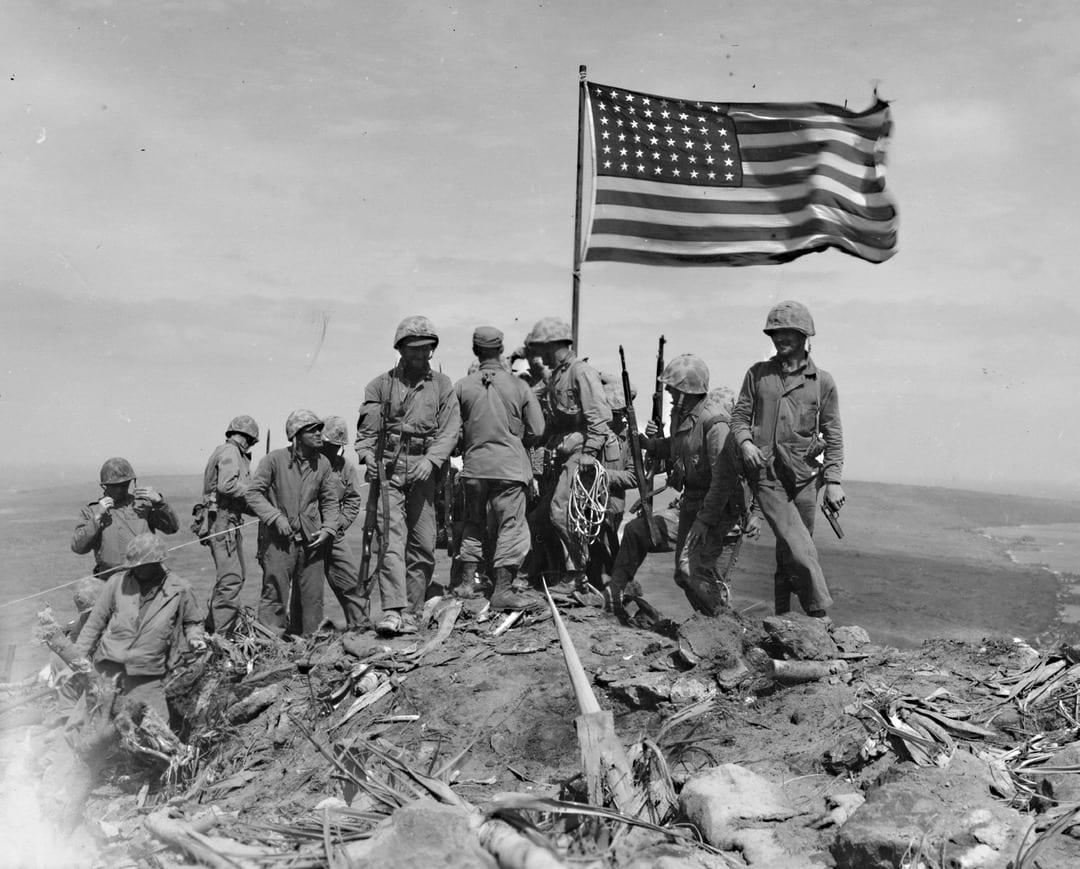 Marines gather around the larger flag after the flag raising. U.S. MARINE CORPS PHOTO