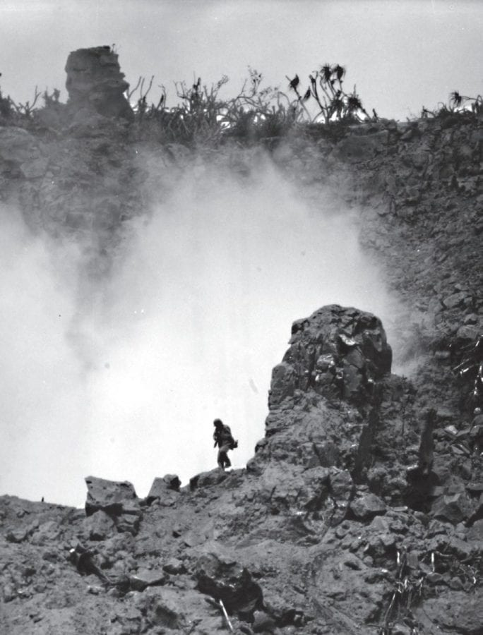 In a deep ravine on the northern ridges of Iwo Jima, Marines use high explosives to destroy Japanese caves and pillboxes. The terrain at the northern end of the island was rocky, volcanic, and stank of sulfur. U.S. MARINE CORPS HISTORICAL CENTER